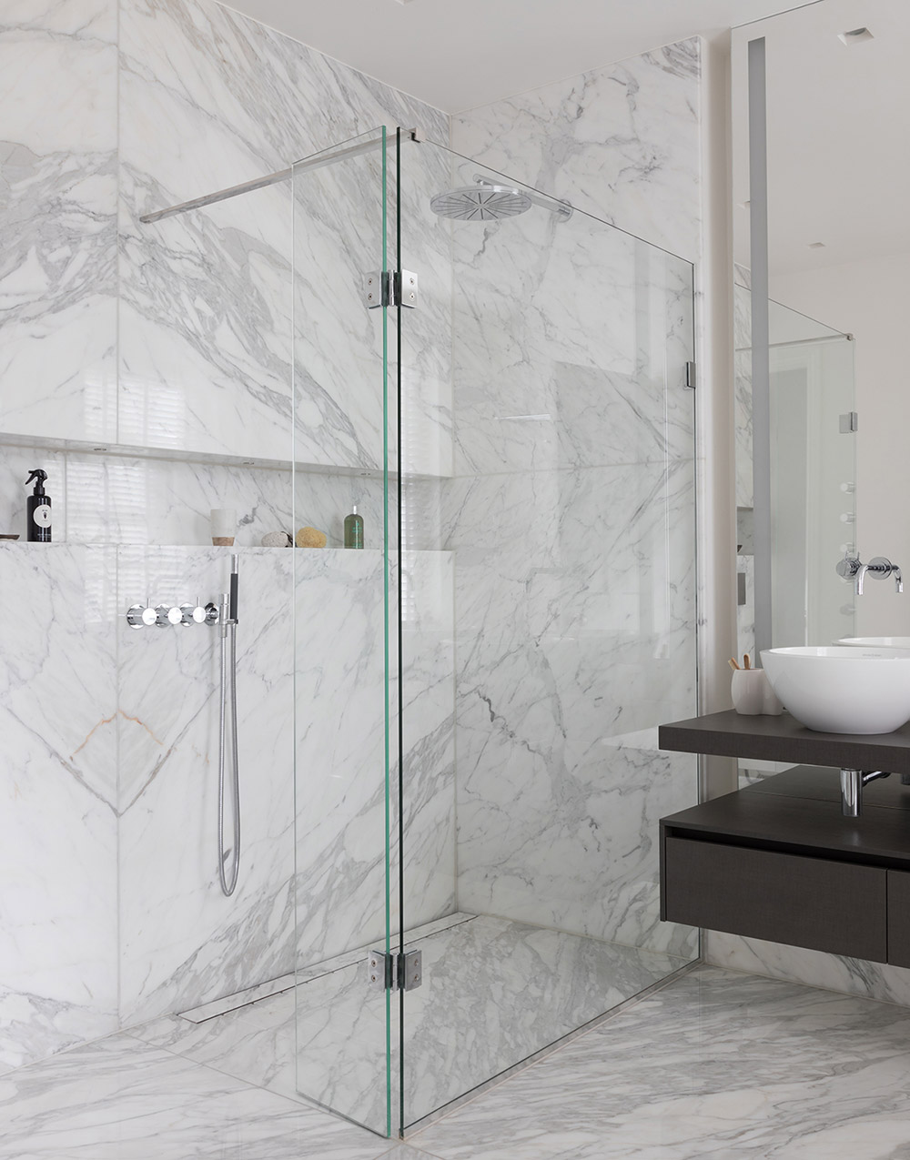 White marble carrara cladded bathroom with walk-in shower